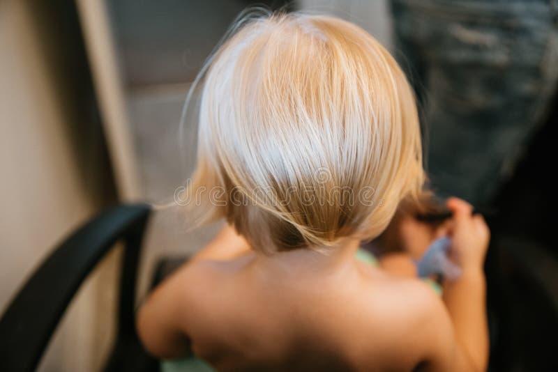 Menino louro pequeno bonito adoravelmente precioso da criança com o cabelo longo que obtém seu primeiro corte do cabelo fotografia de stock royalty free