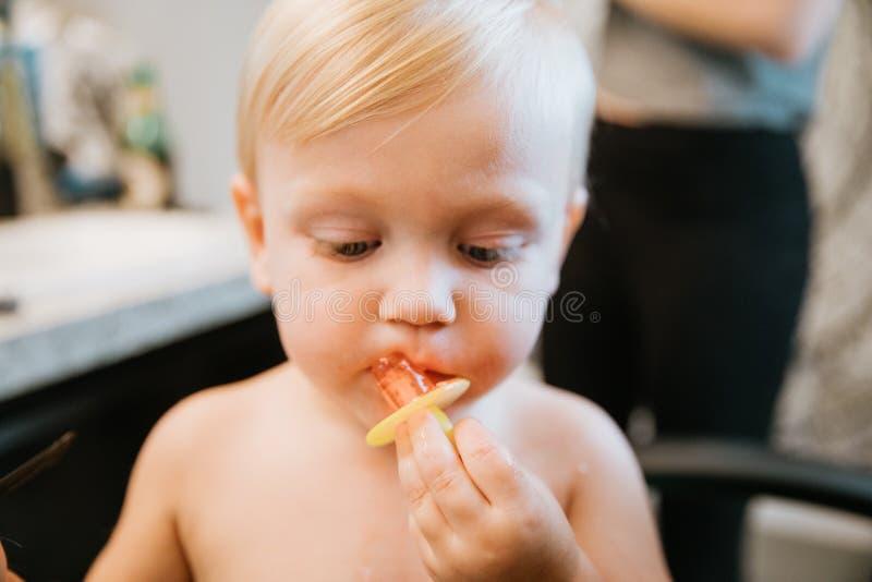 Menino louro pequeno bonito adoravelmente precioso da criança que mostra fora seu penteado novo após ter obtido seu primeiro cort foto de stock