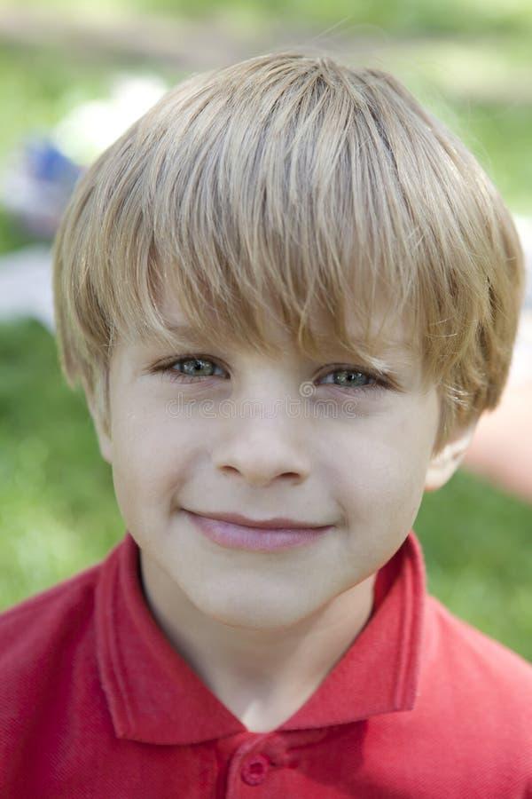 Menino louro pequeno com olhos azuis foto de stock