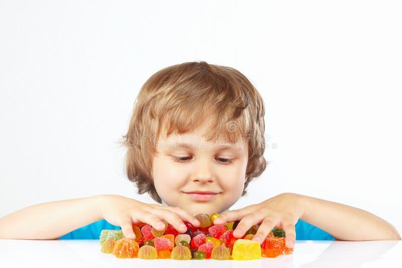 Menino louro pequeno com os doces coloridos da geleia no fundo branco foto de stock