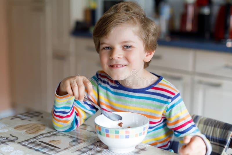 Menino louro pequeno feliz da criança que come cereais para o café da manhã ou o almoço Comer saudável para crianças foto de stock royalty free