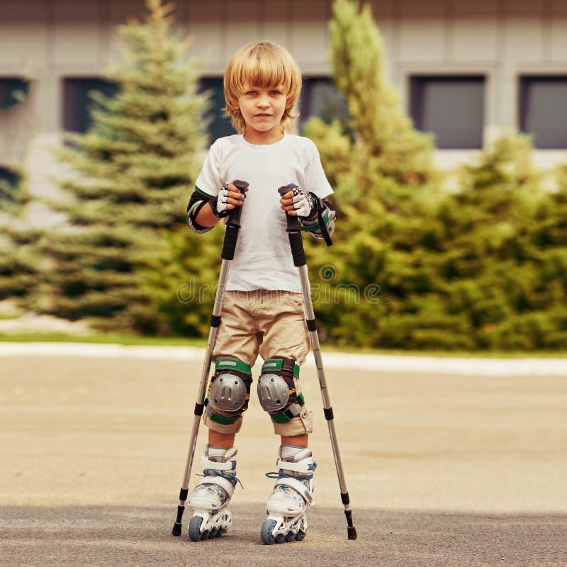 Menino louro que aprende rollerblading foto de stock royalty free