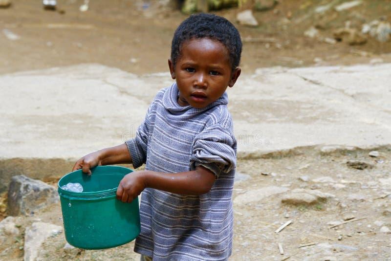 Menino malgaxe pobre que leva a cubeta de água plástica imagem de stock royalty free