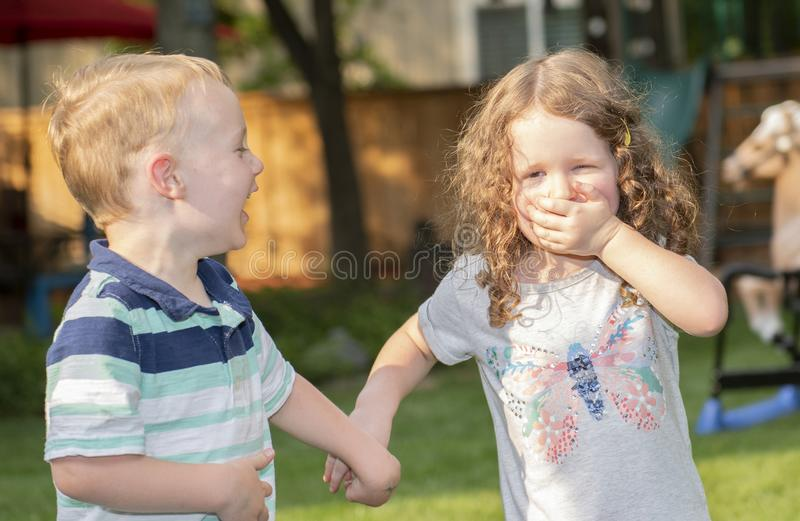 Menino & menina felizes da criança que riem, guardando as mãos e jogando em um quintal foto de stock