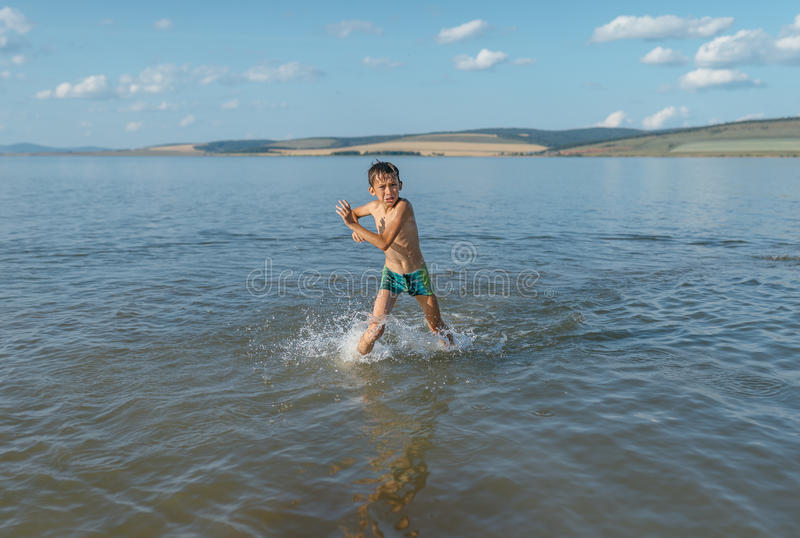 Menino na água muito fria imagens de stock