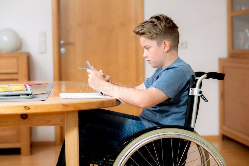 Menino na cadeira de rodas que faz trabalhos de casa e que usa o PC da tabuleta imagens de stock royalty free