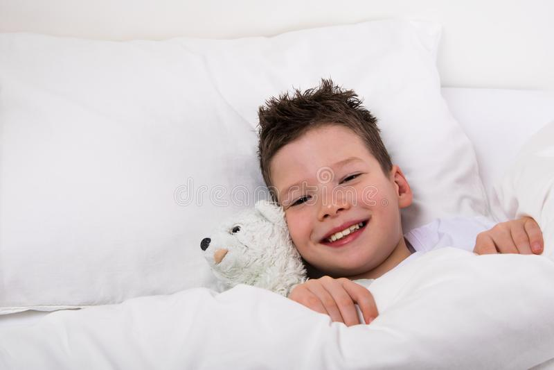 Menino na cama sob uma cobertura com sorriso do brinquedo imagem de stock