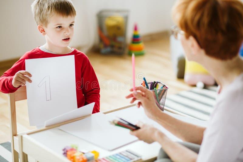 Menino na camiseta vermelha que aprende contar durante atividades extra-curricular imagem de stock