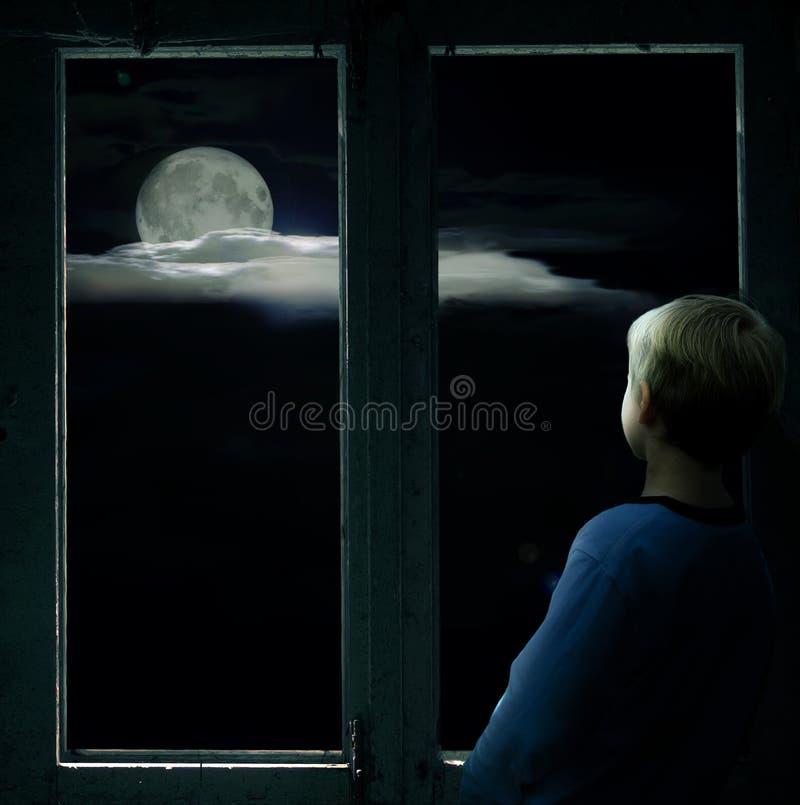 Menino na janela escura que olha a Lua cheia brilhante imagem de stock royalty free