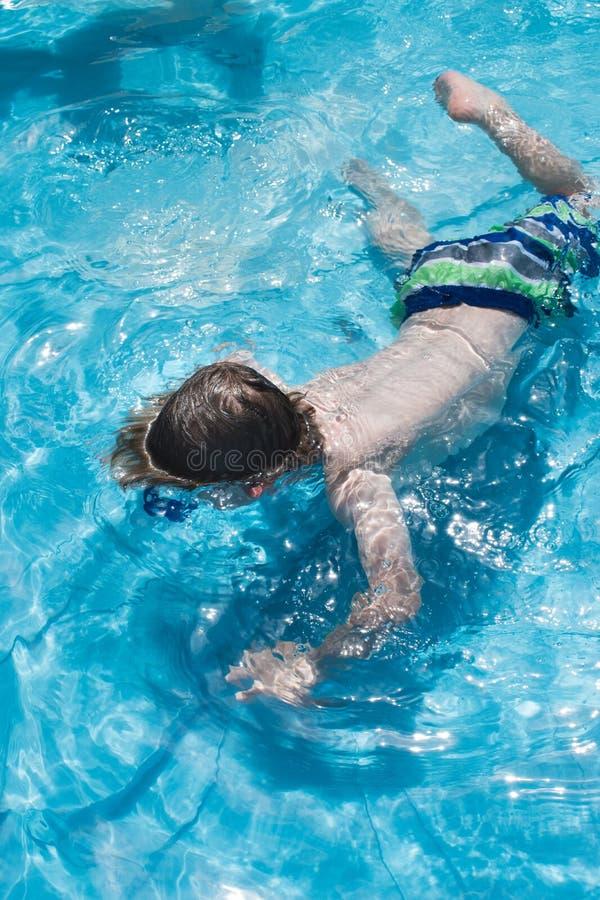 Menino na máscara da natação na piscina subaquática fotos de stock royalty free