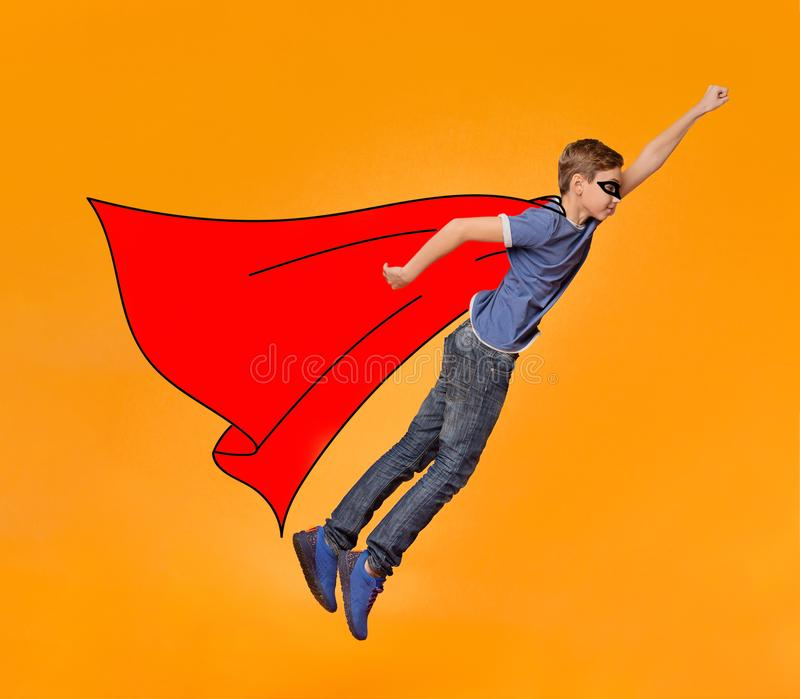 Menino na máscara e no voo vermelho do casaco como o herói fotografia de stock royalty free