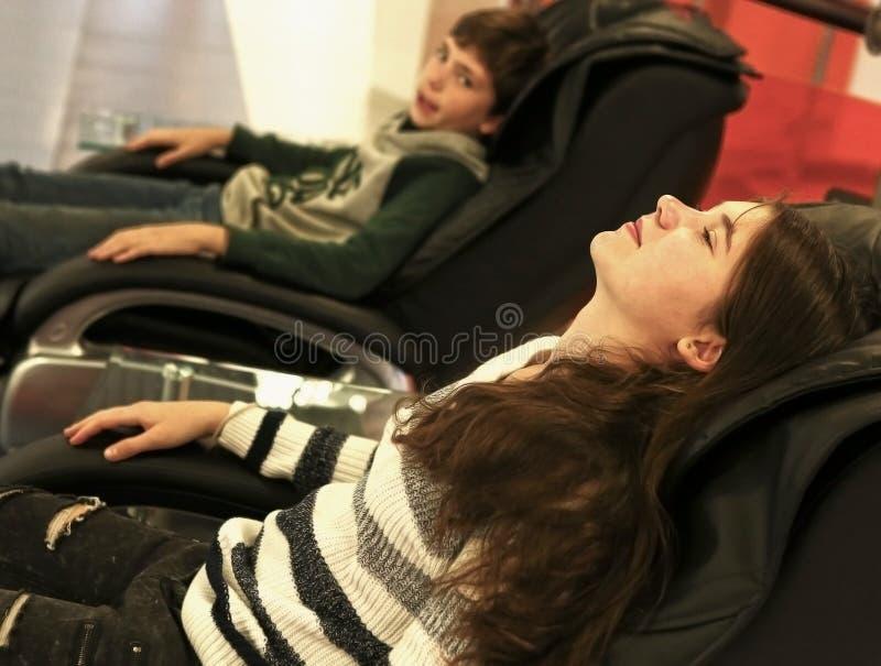 Menino na menina que relaxa na cadeira da massagem imagem de stock