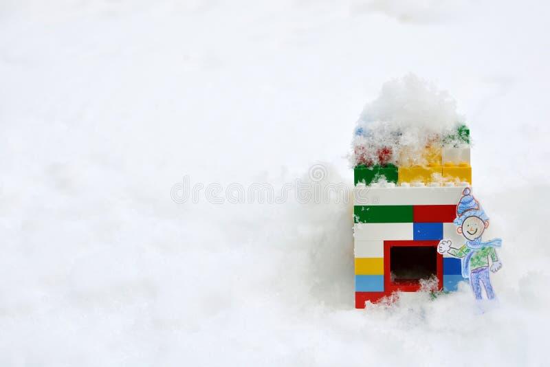 Menino na neve do inverno que acena fora da casa de bloco foto de stock