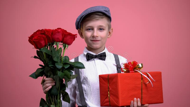 Menino na roupa bonito do vintage com o ramalhete das rosas e da caixa de presente, dia de Valentim foto de stock