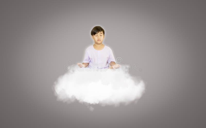 Menino na roupa branca, sentando-se na meditação com espírito puro, nas nuvens calmas que flutuam, conceito de descobrir a verdad fotos de stock