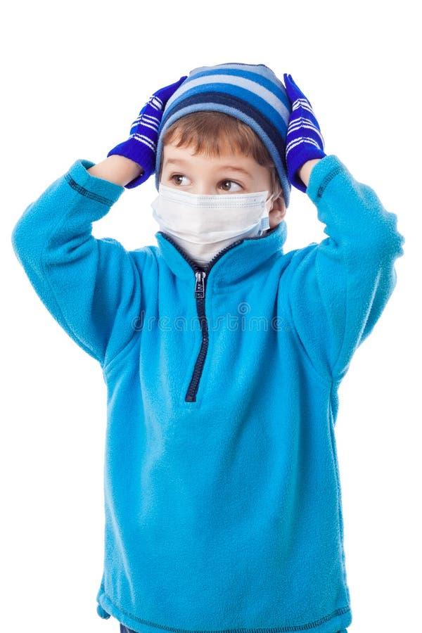 Menino na roupa do inverno e na máscara médica foto de stock royalty free