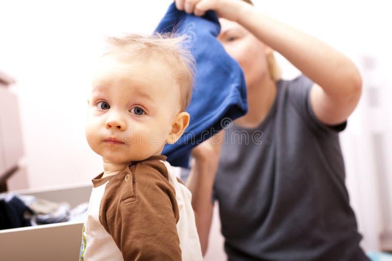 Menino na seleção da roupa com sua matriz. fotografia de stock