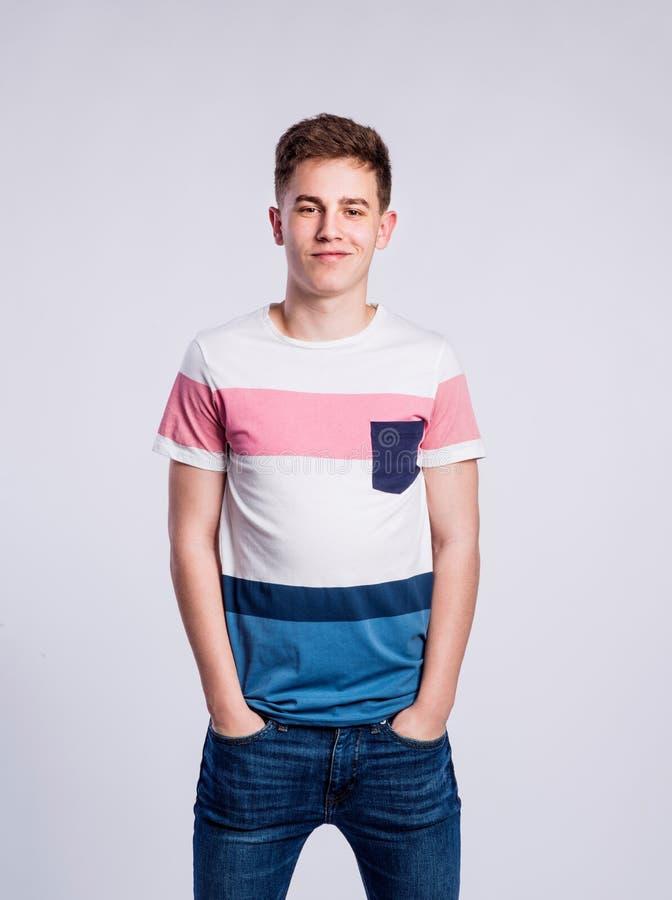Menino nas calças de brim e no t-shirt, homem novo, tiro do estúdio fotografia de stock royalty free
