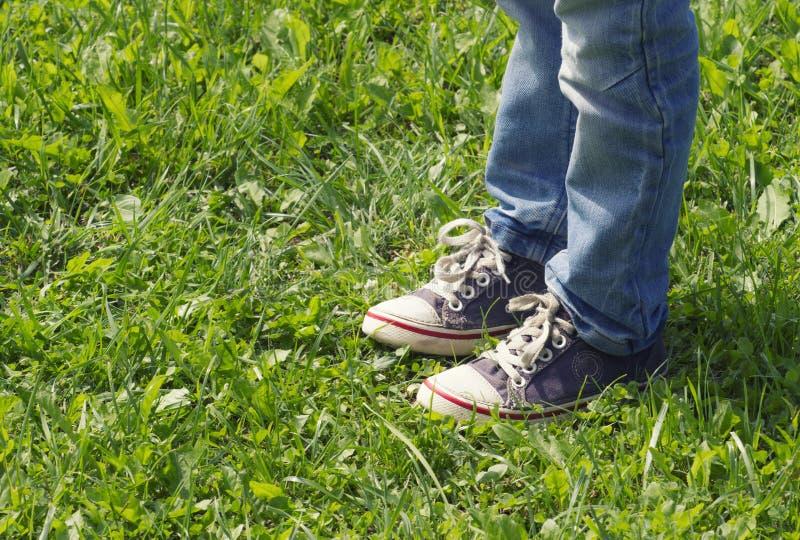 Menino nas sapatilhas azuis e nas calças de brim que estão no dia ensolarado de grama verde no verão Feche acima do tiro do pé Im foto de stock