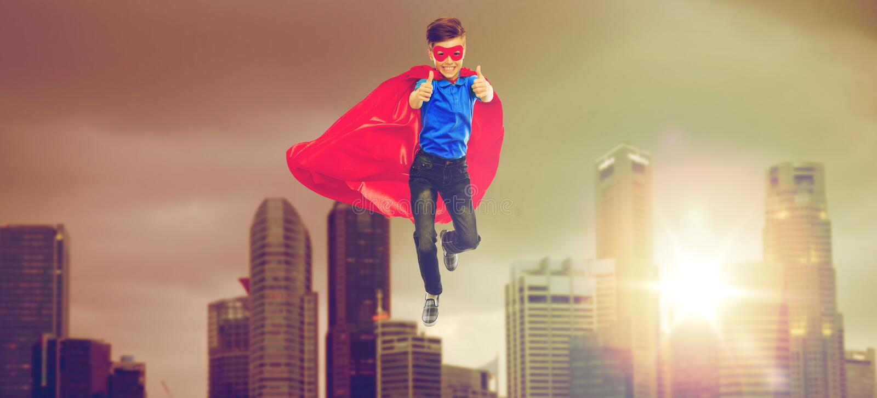 Menino no cabo do super-herói e máscara que mostra os polegares acima imagens de stock royalty free