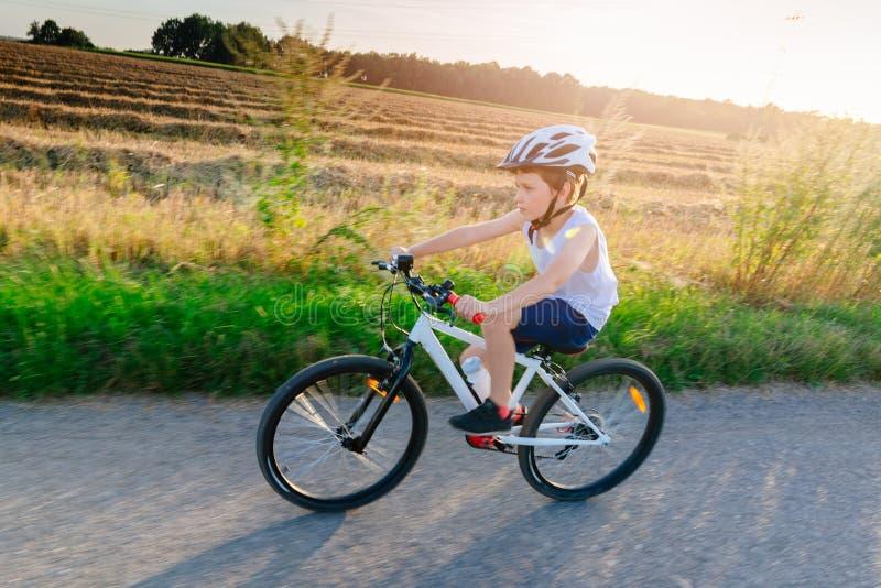Menino no capacete branco que monta sua bicicleta imagem de stock