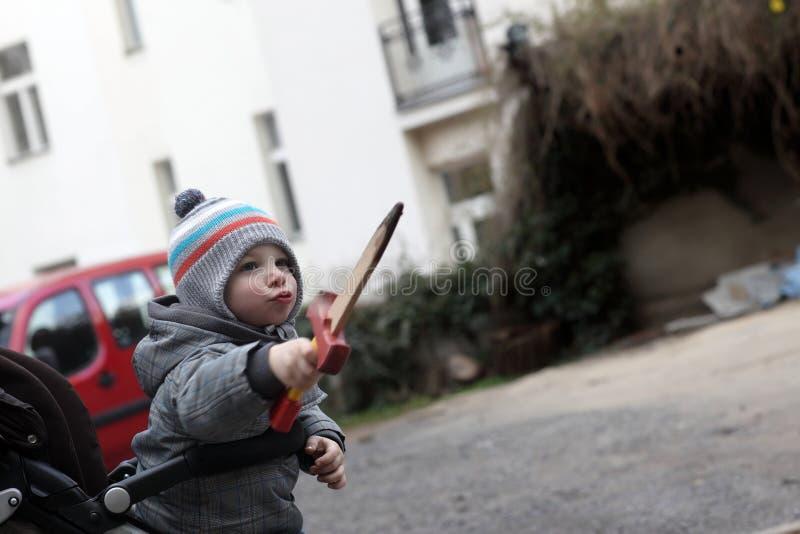 Menino no carrinho de criança com um brinquedo do punhal imagem de stock