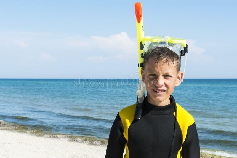 Menino no divingsuit e na máscara e tubo de respiração no fundo do mar imagem de stock