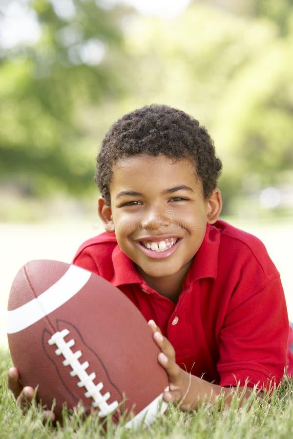 Menino no parque com futebol americano fotografia de stock