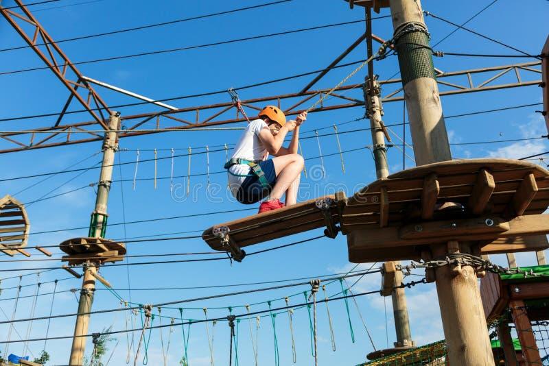 Menino no parque da aventura da floresta A criança no capacete alaranjado e na camisa branca de t escala na fuga alta da corda Es imagem de stock