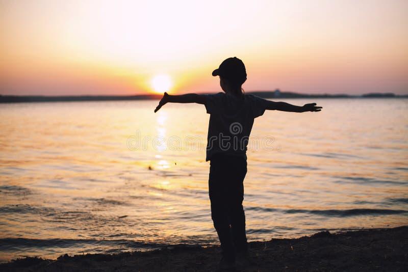 Menino no por do sol na praia e levantado suas mãos acima foto de stock