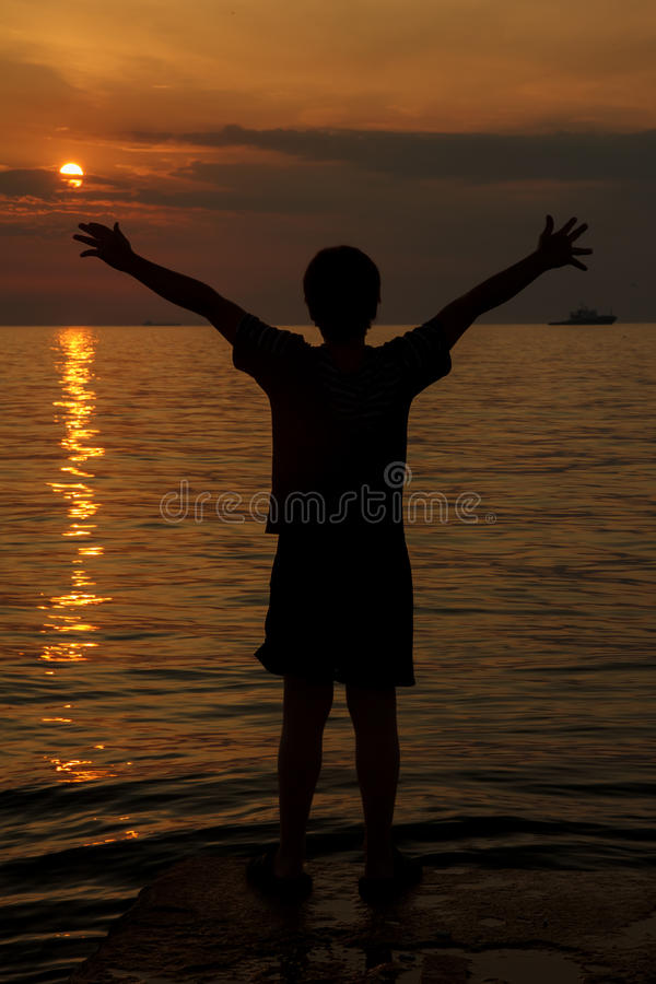 Menino no por do sol sobre o mar foto de stock royalty free