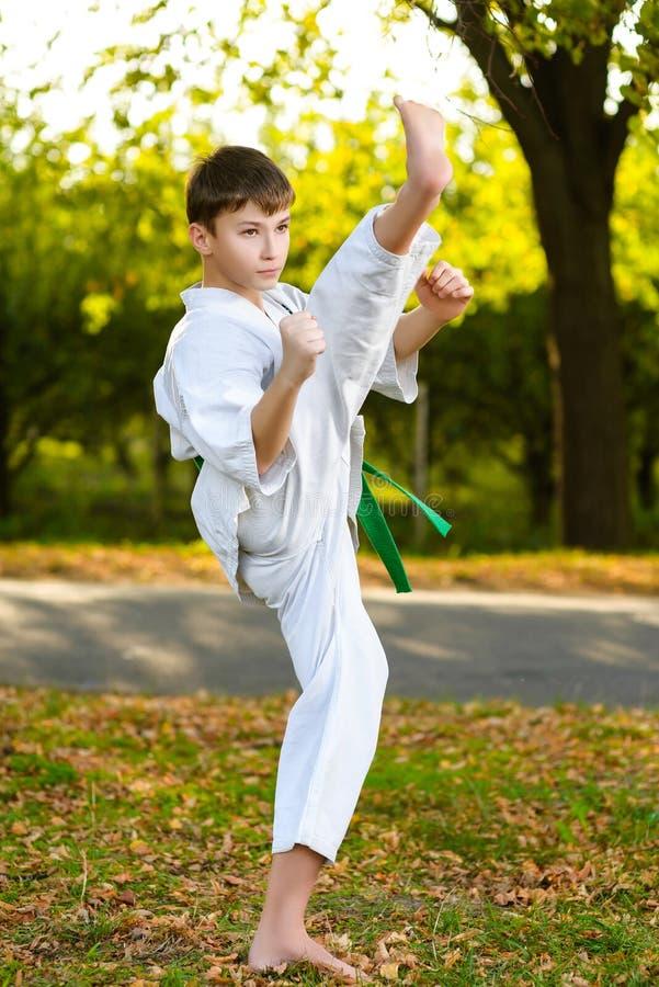 Menino no quimono branco durante o karaté do treinamento fotos de stock royalty free