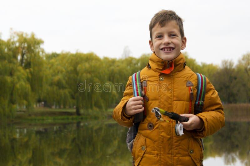 Menino no revestimento amarelo que guarda a vara de pesca fora na lagoa durante o dia fresco do outono imagens de stock royalty free