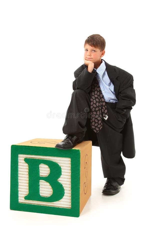 Menino no terno com bloco do alfabeto imagem de stock royalty free