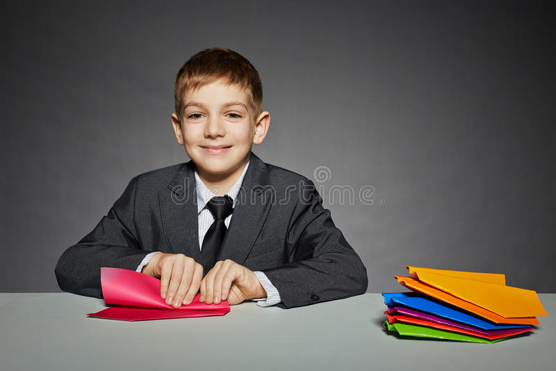 Menino no terno que faz o plano de papel vermelho imagem de stock