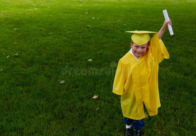 Menino no vestido pré-escolar amarelo da graduação, sustentando seu diploma fotografia de stock