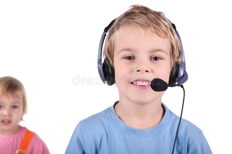 Menino nos auriculares com menina fotografia de stock