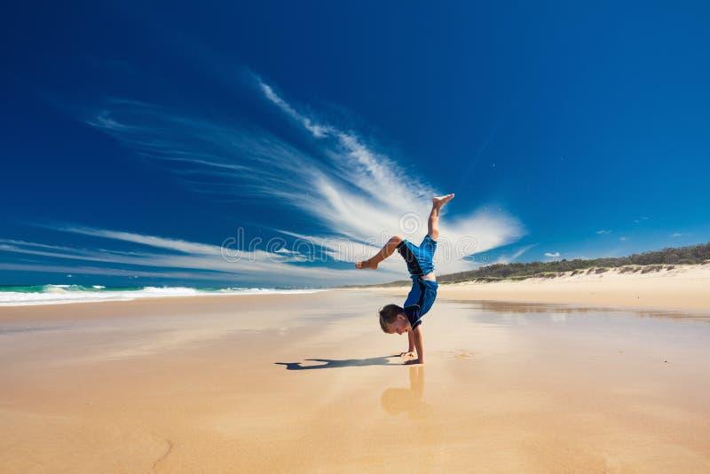 Menino novo acrobático que executa o suporte da mão na praia fotografia de stock royalty free