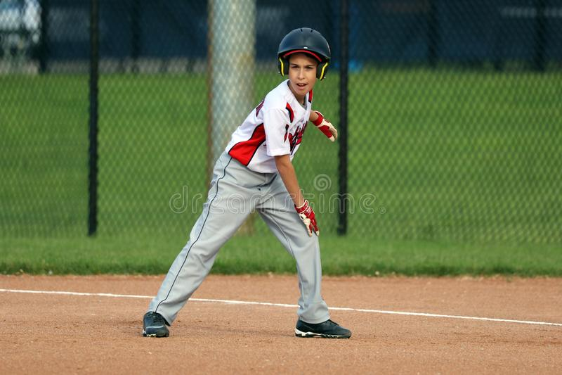 Menino novo bonito considerável que joga o basebol que espera e que protege a base imagem de stock
