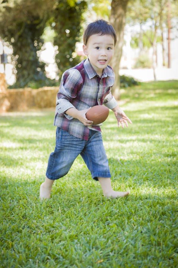 Menino novo bonito da raça misturada que joga o futebol fora fotos de stock
