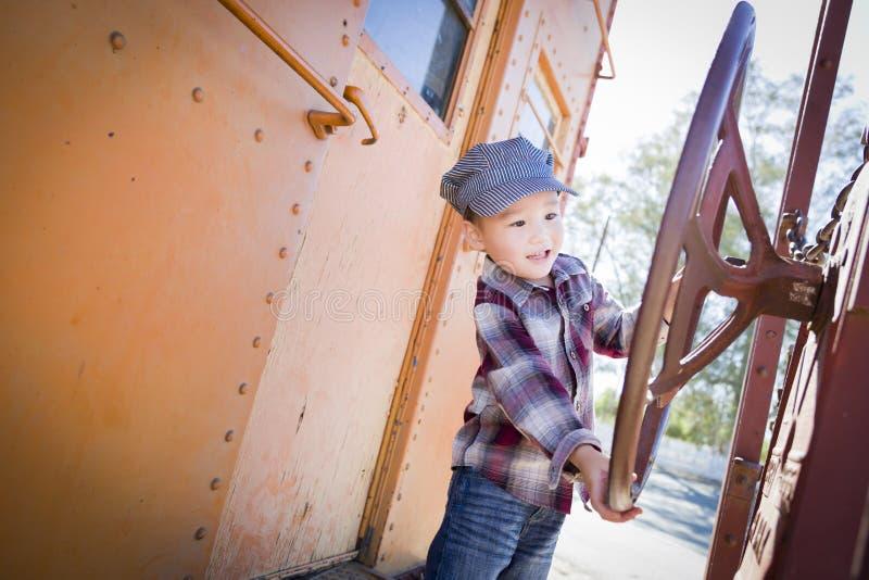 Menino novo bonito da raça misturada que tem o divertimento no carro de estrada de ferro fotografia de stock royalty free