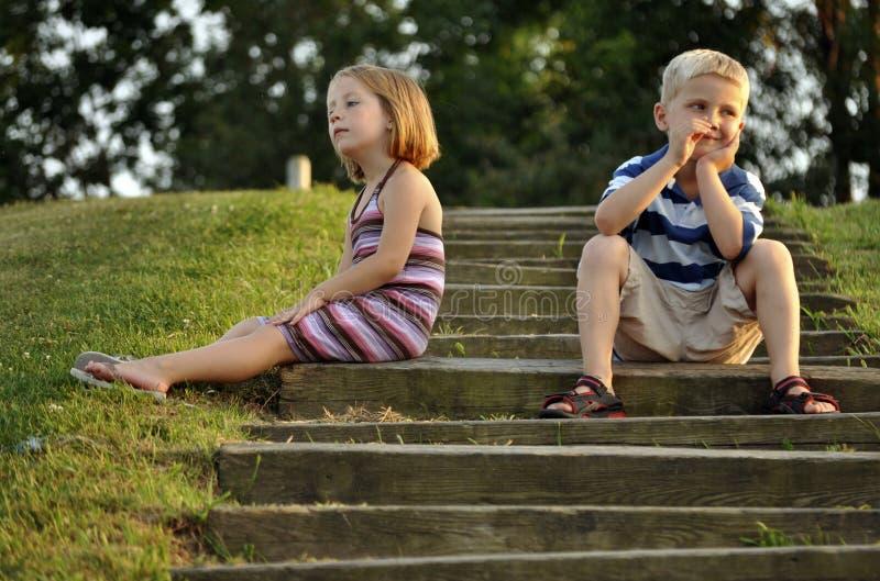Menino novo bonito e menina que sentam-se em etapas do parque fotografia de stock royalty free