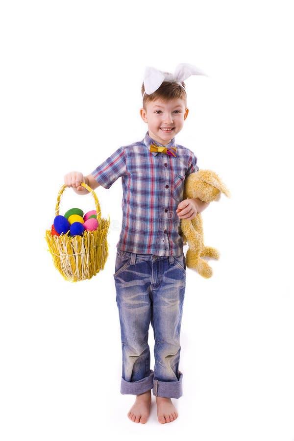 Menino novo bonito em uma imagem de um coelhinho da Páscoa com ovos imagens de stock
