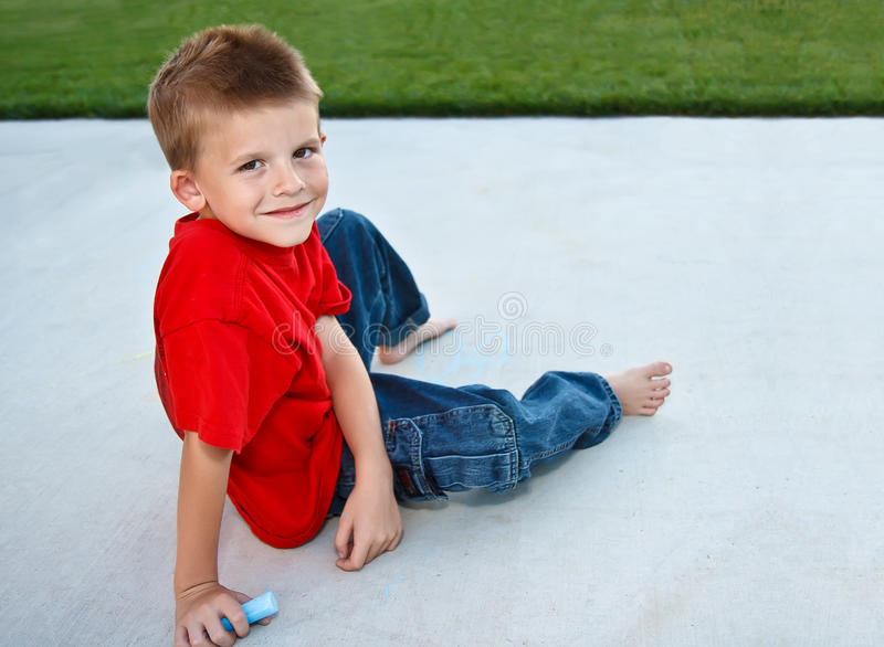 Menino novo bonito que joga com giz do passeio fotografia de stock