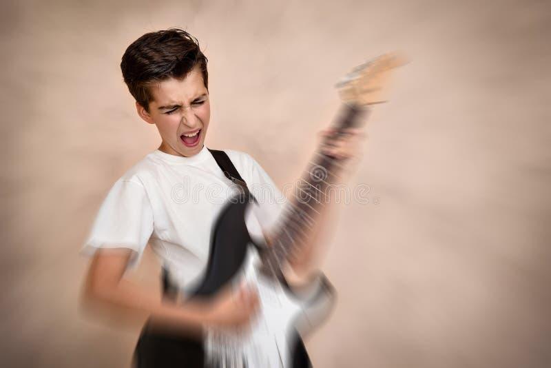 Menino novo bonito que joga a guitarra elétrica fotografia de stock royalty free