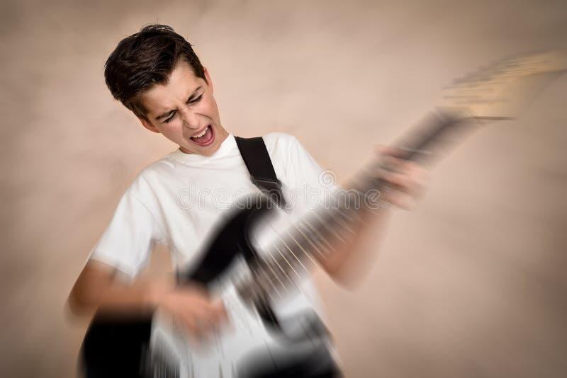 Menino novo bonito que joga a guitarra el?trica imagem de stock royalty free