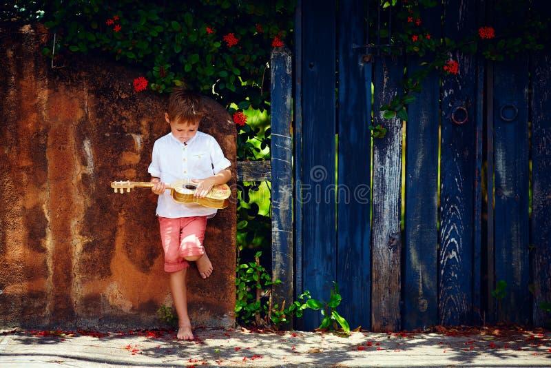 Menino novo bonito que joga a guitarra perto da cerca velha do verão foto de stock