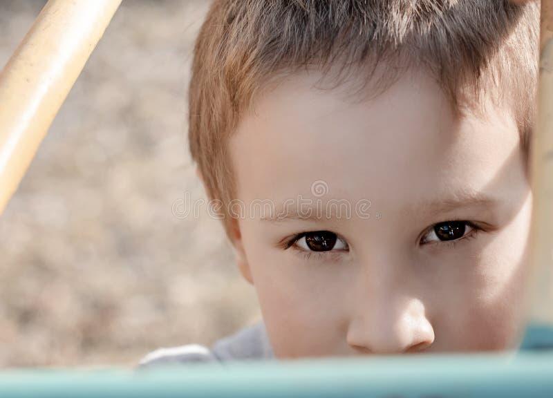 Menino novo bonito que olha a câmera no campo de jogos das crianças Criança do pré-escolar que tem o divertimento no campo de jog fotos de stock