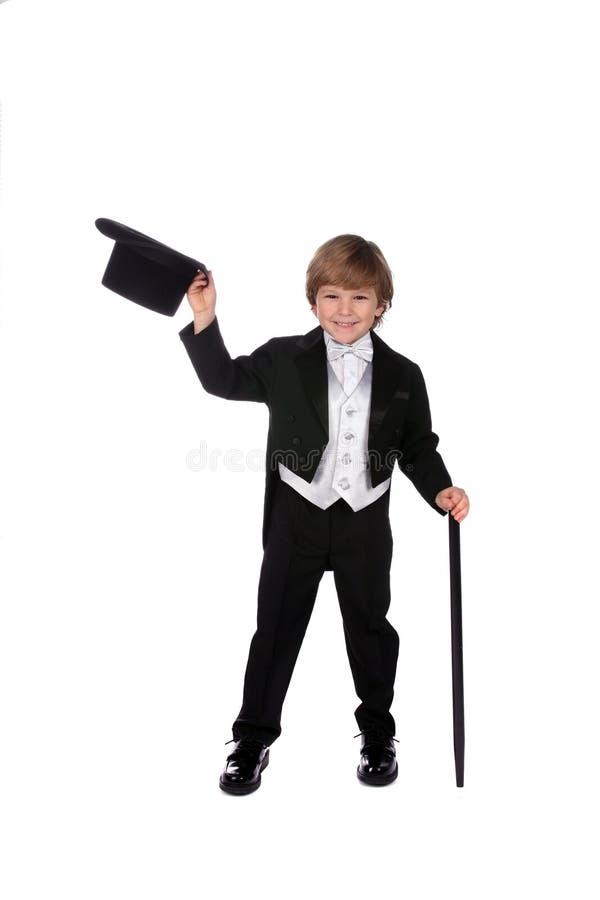 Menino novo brincalhão no tux preto que tira seu chapéu imagens de stock royalty free