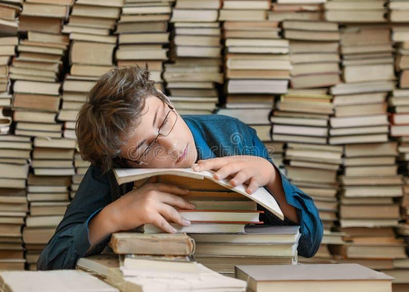 Menino novo cansado e livros Menino novo cansado que senta-se e que dorme com sua cabeça nos livros foto de stock royalty free
